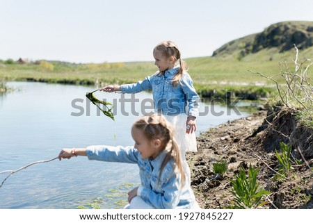 Photo of happy daughter and mother have outdoor stroll against city background, walk their dog, keep Stock photo © vkstudio