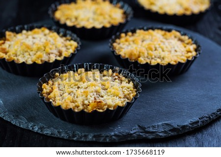 Small and delicious apple pies or apple crumble on black background Stock photo © brebca