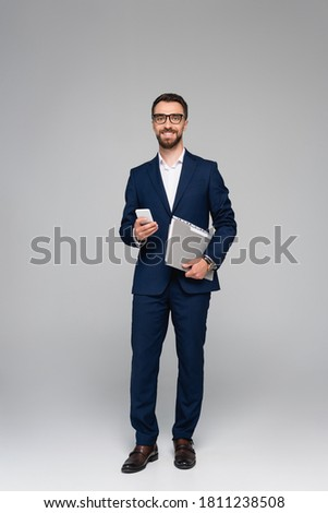 Studio shot of a businessman with blue folder on gray background Stock photo © deandrobot