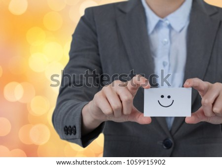 Stock fotó: Midsection of businesswoman holding smiley face on card