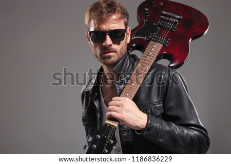 smiling man holding electric guitar on shoulder looks to side stock photo © feedough