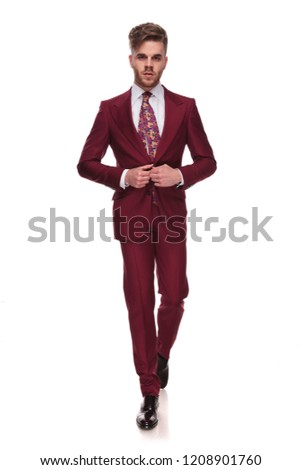 seductive elegant man stepping forward and buttoning grena suit Stock photo © feedough