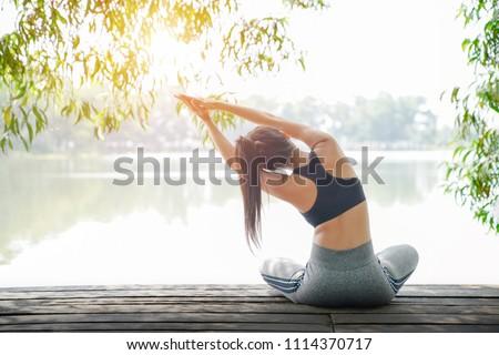 Mooie jonge vrouw oefenen yoga park zonsondergang Stockfoto © Len44ik