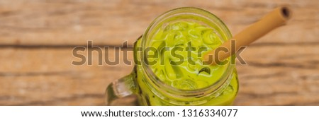 Green tea latte with ice in mason jar and straw on wooden background. Homemade Iced Matcha Latte Tea ストックフォト © galitskaya