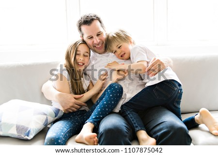 Father and his nine years kid girl and 5 years boy on the sofa at home Foto stock © Lopolo