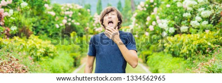 young man blowing nose in front of blooming tree spring allergy concept banner long format stock photo © galitskaya