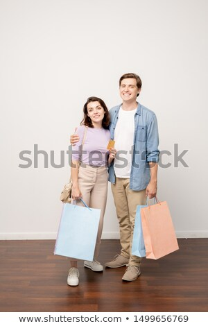 happy couple of young shoppers with paperbags and credit card standing by wall stock photo © pressmaster