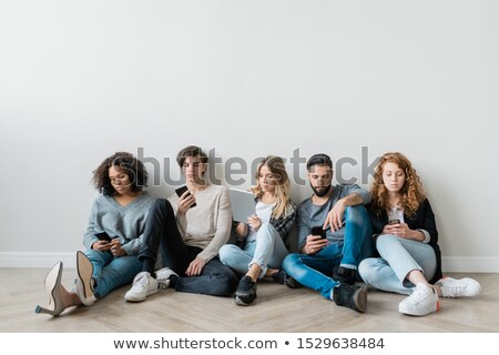 Group of serious millennials with smartphones and touchpad scrolling in gadgets Stock photo © pressmaster