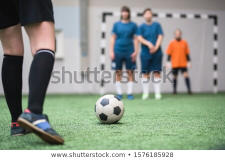 Soccer ball on green footaball field with legs of sportswoman going to kick it Stock photo © pressmaster
