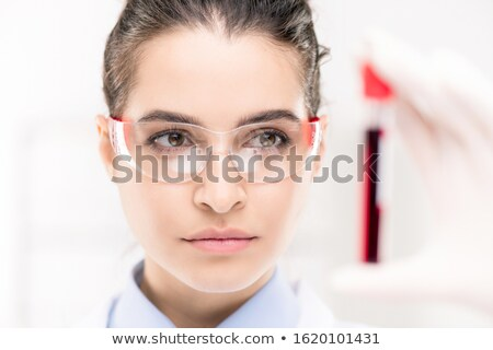 Young serious female in protective eywear looking at flask with new vaccine Stock photo © pressmaster