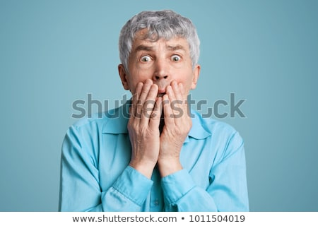 Shocked man covering mouth with hands over blue background Stock photo © GVS