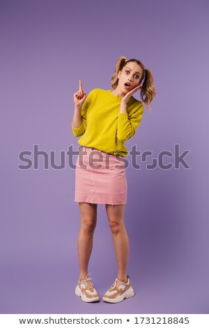 Image of shocked pretty woman with two tails pointing finger upward Stock photo © deandrobot