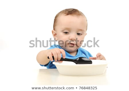 Cute adorable one year old baby with green eyes eating on table, spoon and plate Stock photo © zurijeta