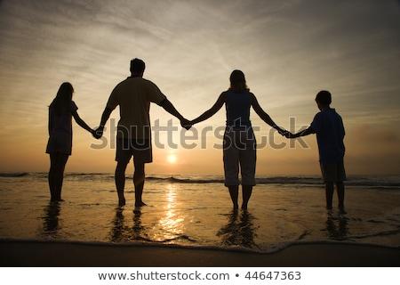 család · kéz · a · kézben · tengerpart · néz · naplemente · sziluett - stock fotó © kotenko
