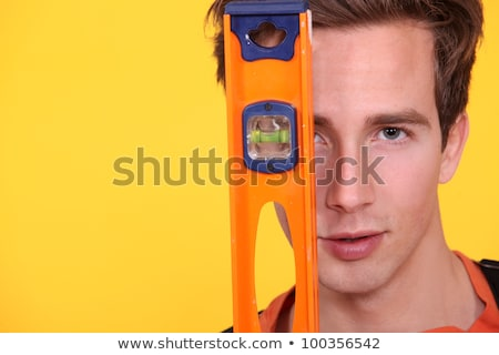 Carpenter covering his face with spirit-level Stock photo © photography33