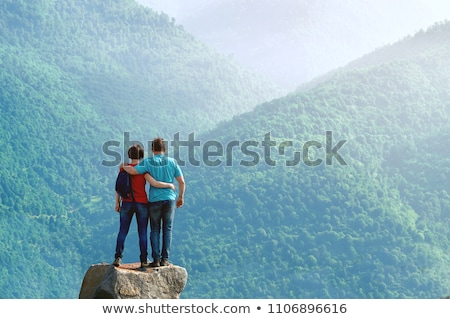 young man on a rock in the middle of the nature stock photo © aetb