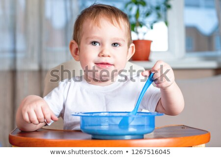 Baby feeding himself with spoon stock photo © sdenness