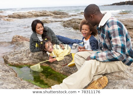 Young family with fishing net on rocks Stock photo © monkey_business
