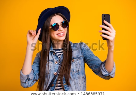 Young happy woman making self photo with her smartphone Stock photo © deandrobot