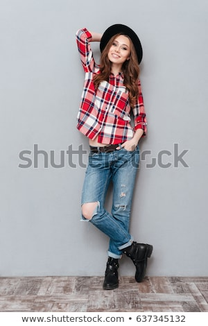 Young woman in plaid shirt posing on gray background Stock photo © deandrobot