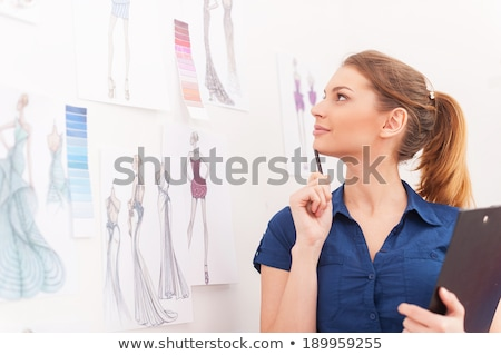fashion designer creating new clothes and drawing sketches on clipboard stock photo © deandrobot