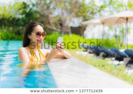 portrait of a girl in bikini using smartphone stock photo © deandrobot