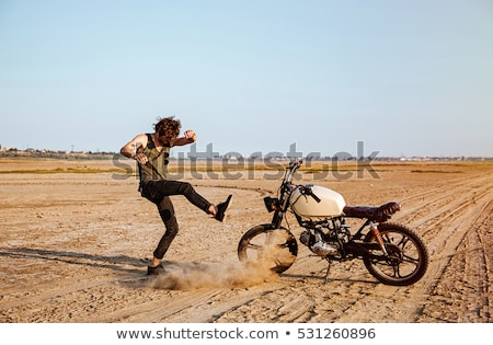 Man making dust standing near his motorcycle Stock photo © deandrobot