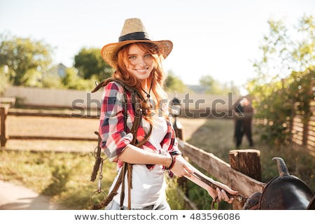 happy redhead woman cowgirl preparing saddle for riding horse stock photo © deandrobot