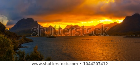 Sunset over the mountains and sea with clouds Stock photo © All32
