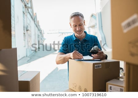 deliveryperson standing with van with clipboard and box smiling stock photo © monkey_business