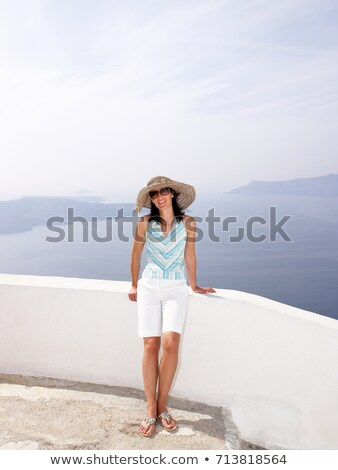 Woman leaning on a low wall, sea view Stock photo © IS2