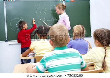 primary school teacher helping boy learn numbers stock photo © monkey_business