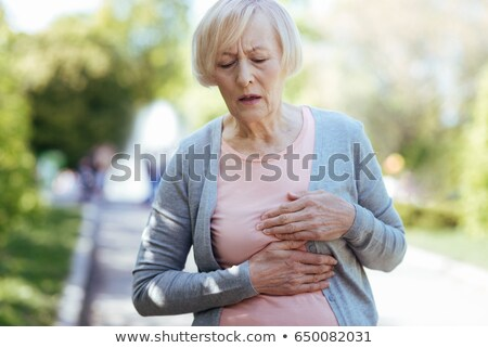 Puzzled aging woman having heart attack outdoors Stock photo © manaemedia