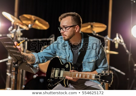 man with guitar writing to music book at studio Stock photo © dolgachov