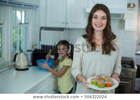 Mother Holding Cupcake While Looking At Her Daughter Stock photo © AndreyPopov