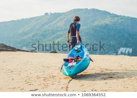 молодым человеком байдарках берега небе человека Сток-фото © galitskaya