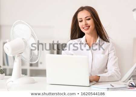 Businesswoman Enjoying Breeze With Electric Fan Stock photo © AndreyPopov