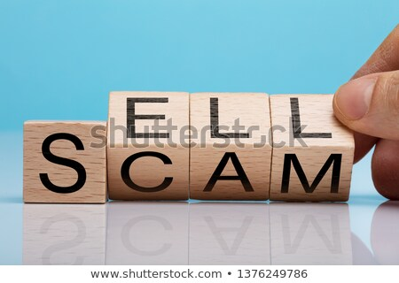 Human Hand Holding Wooden Block With Sell And Scam Text Stock photo © AndreyPopov