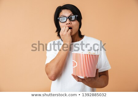 portrait of a scared young asian man eating popcorn stock photo © deandrobot