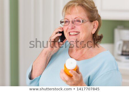 Senior Adult Woman on Cell Phone Holding Prescription Bottle Stock photo © feverpitch