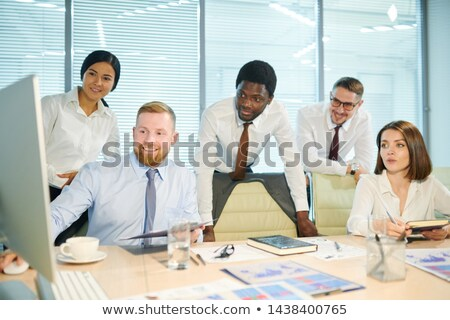 Group of intercultural brokers watching webinar or online conference Stock photo © pressmaster