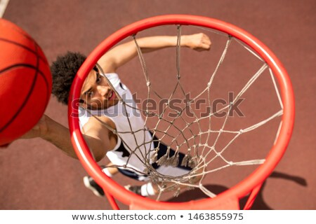View of basket with net and young player throwing ball below Stock photo © pressmaster