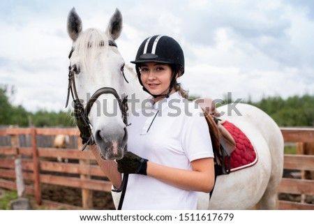 Young smiling woman in equestrian outfit standing close to white racehorse Stock photo © pressmaster