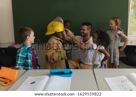 Front view of male Caucasian firefighter helps to wearing fire uniform to schoolkid with all the sch Stock photo © wavebreak_media