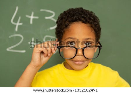 Rear view of happy mixed-race schoolboy looking over spectacle against greenboard in a classroom at  Stock photo © wavebreak_media