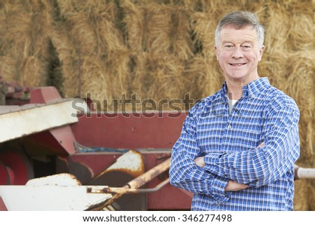Farmer Standing In Front Of Straw Bales And Old Farm Equipment Stock photo © HighwayStarz