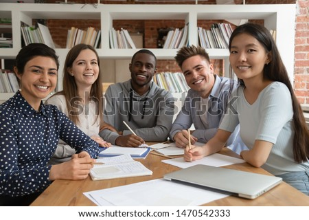 Group of happy young college friends gathered by table in cafe after classes Stock photo © pressmaster