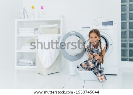 Positive kid with pigtails sticks out head from washing machine, has fun and holds shirt, prepares f Stock photo © vkstudio