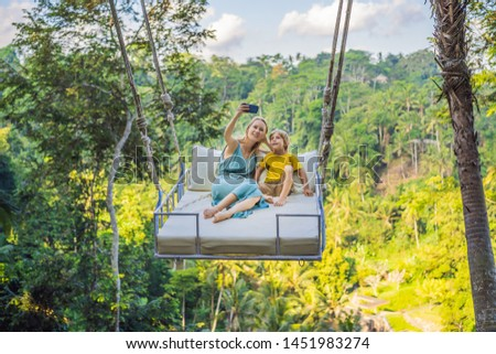 Mother and son swinging in the jungle rainforest of Bali island, Indonesia. Swing in the tropics. Sw Stock photo © galitskaya