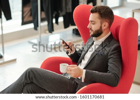 Young well-dressed businessman with cup of tea texting in smartphone Stock photo © pressmaster